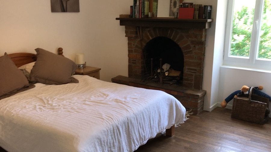 Bedroom 3 with king double bed, log fireplace and views over the upper orchard.