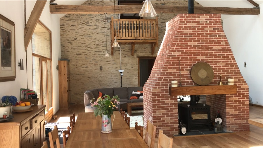 The double-height Banquet Hall, with large dining table, breakfast bar, central brick chimney and 12-seater sofa lounge.