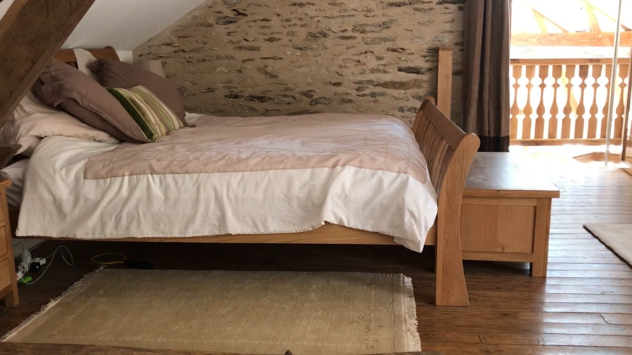 The master bedroom's bed, with a glimpse of the balcony view through the gite