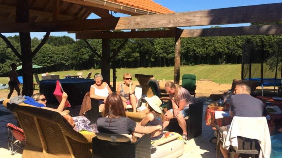 Socialising on the gite terrace patio with back-view of the grasslands to the forest far away